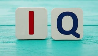Intelligence quotient. Word IQ on blue wooden background