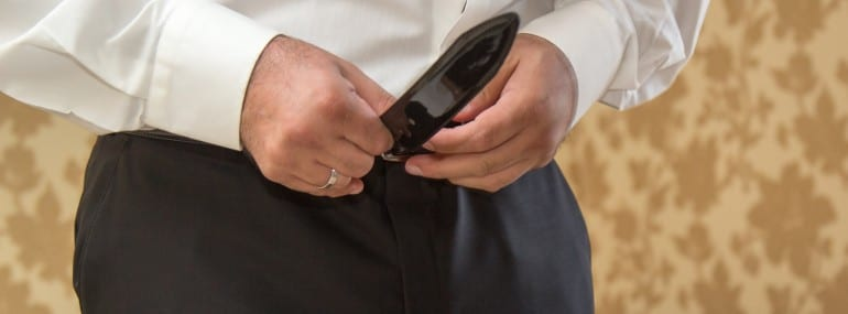 Groom holding hands on the belt, wedding suit