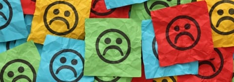 Crumpled adhesive notes with sad faces