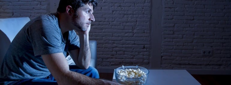 television addict man sitting on sofa watching TV eating popcorn using remote control looking bored