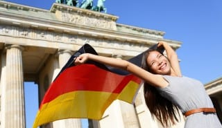 German flag woman happy at Berlin Brandenburg Gate