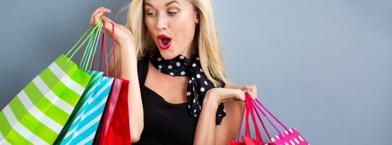 Happy young blonde woman with shopping bags