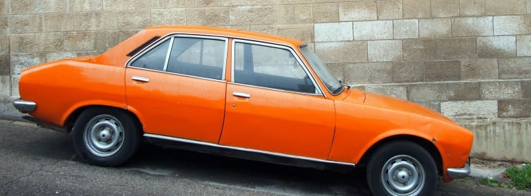 Vintage Old Orange Car on the Streets of Jordan Against Brick Wall background