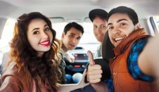 A company of four friends makes selfie inside the car