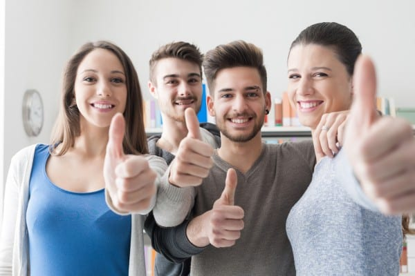 Cheerful students with thumbs up