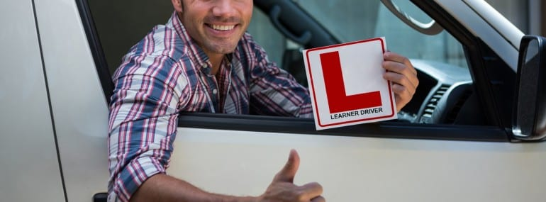 Young man gesturing thumbs up holding a learner driver sign