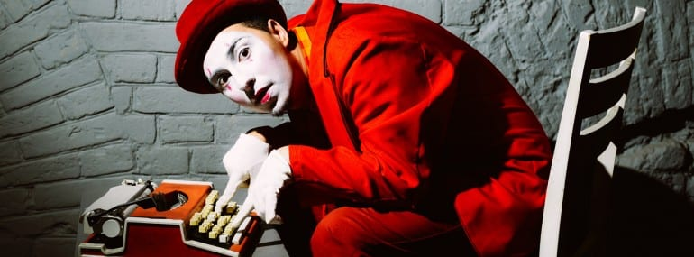 Mime in a red suit prints on a typewriter