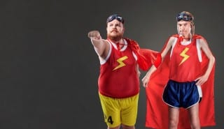 Two funny men in suits of superheroes. Thin and fat people
