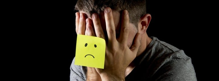 young man suffering depression and stress alone with sad post it