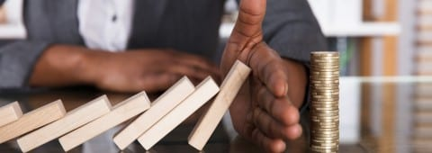 Human Hand Stopping Wooden Blocks From Falling On Stacked Coins