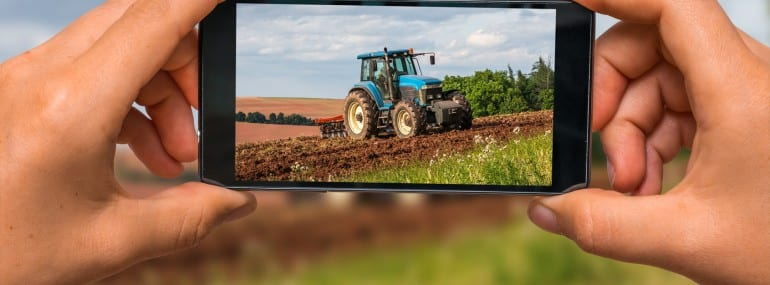 Taking photo of tractor at work on a field with mobile phone