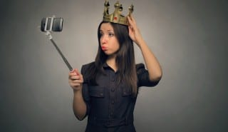 Young caucasian girl with golden crown above her head makes selfie photo on mobile phone by using selfie stick. Egoistical person concept.