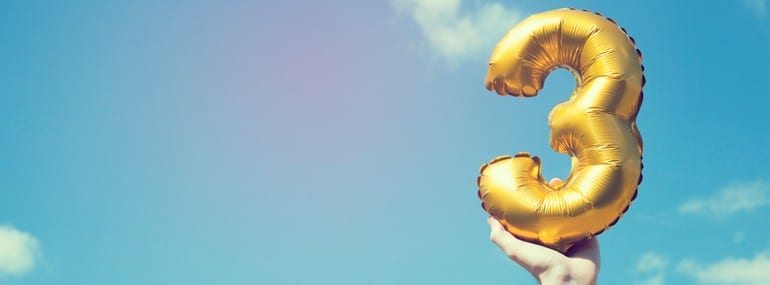 A hand holds a balloon shaped as the number 3 with a blue sky background