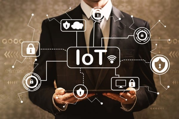 IoT security theme with businessman holding a tablet computer