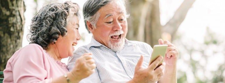 happy senior couple exciting with smartphone