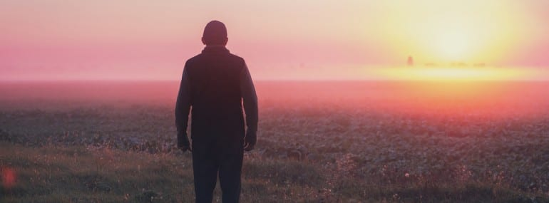A man stands in the field in the early morning and looks at the sunrise